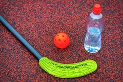 Floorball ball near stick and water bottle. In summer day stock image