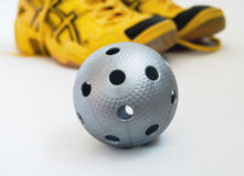 Floorball ball and shoes. A gray floorball ball and yellow shoes. Focus on the ball Royalty Free Stock Photography