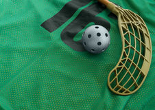 Floorball equipment 1. Floorball ball and stick on a green jersey Stock Image