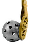 Floorball equipment 2. A gray floorball ball and a golden stick Royalty Free Stock Images