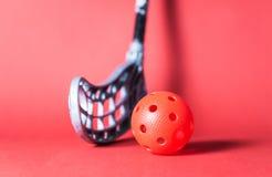 Floorball piłka przeciw czerwonemu tłu i kij Fotografia Royalty Free