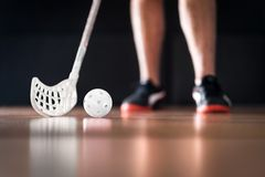 Floorball player standing with white ball and stick. Floor hockey concept. stock photos