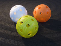Floorball. Three colored floorball balls on black background Royalty Free Stock Images