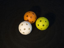 Floorball. Three colored floorball balls on black background Royalty Free Stock Photography