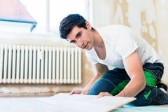 Floorer che lavora nella casa nel progetto di miglioramento Immagine Stock