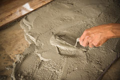 Flooring cement Home renovation, tiles. Home renovation, worker prepare tile with cement for placing Stock Photo