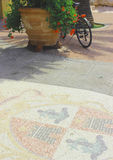 Flooring with coat of arms and bicycle in Porto Azzurro Stock Photos
