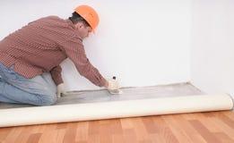 Flooring installation. Construction worker during flooring installation Stock Image