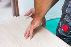 Flooring renovation. Handyman renovating house, installing laminate wood flooring with care Royalty Free Stock Photo