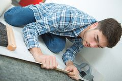 Flooring setter examining material underneath. Flooring setter examining the material underneath Royalty Free Stock Images
