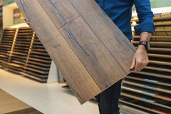 Free Flooring Store Salesman With Laminate Floor Sample Panel Stock Images - 168010824
