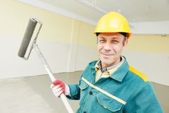 Flooring worker with roller. Male plasterer portrait during floor covering works with self-levelling cement mortar Royalty Free Stock Photography