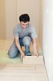 Flooring works with laminated board. Young worker carpenter laying a floor with laminated flooring boards stock image