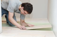 Flooring works with laminated board. Young worker carpenter laying a floor with laminated flooring boards royalty free stock photo