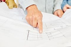 Floorplan and architect pointing and making decisions. About building construction royalty free stock photo