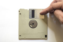 Floppy disc on a white isolated background. Detail of floppy disc on a white isolated background. A hand moves the retractable metal sleeve, that covers a window Royalty Free Stock Photos