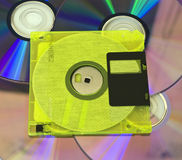 Floppy disk. Yellow floppy disk on background of cd Royalty Free Stock Photography