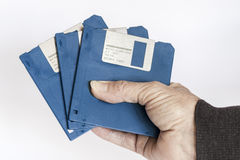 Floppy disks in the hand. Hand of a woman is holding three floppy disks; white background Royalty Free Stock Image