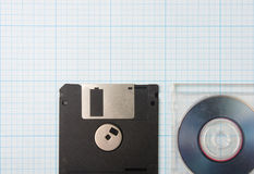 Floppy disks and mini-CD. Vintage background - computer floppy disks and mini-CD on the blueprint paper, toned Royalty Free Stock Image