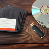 Floppy disks, USB flash drive and disks on a wooden background royalty free stock photography