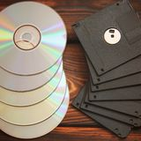 Floppy disks and disks on wooden background royalty free stock photos