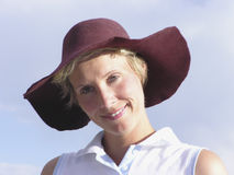 FloppyHat01. Woman with maroon hat smiling royalty free stock photography