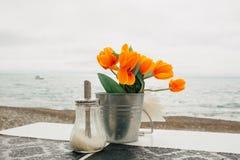Flor alaranjada em uma cubeta e em um açucareiro Foto de Stock Royalty Free