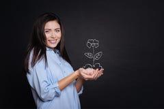 Flor alegre do holdign da mulher fotografia de stock