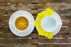 Flor amarela do algodão de seda com pares de copo de chá no prato cerâmico Imagens de Stock Royalty Free