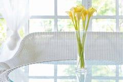 Flor amarilla en florero en fondo del travesaño de la tabla y de la ventana Vinta Fotos de archivo libres de regalías