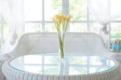 Flor amarilla en florero en fondo del travesaño de la tabla y de la ventana Vinta Foto de archivo