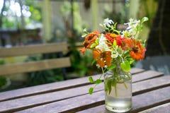 Flor anaranjada en la tabla Imagen de archivo libre de regalías