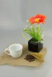 Flor anaranjada en un florero con la taza de café en aislante de la materia textil del yute Foto de archivo libre de regalías