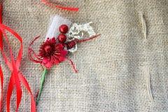 Flor artificial vermelha com as fitas festivas vermelhas em um fundo da textura de linho velha marrom da tela, material natural d imagem de stock