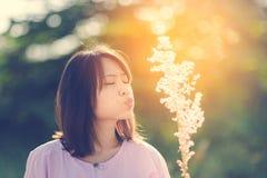 Flor asiática linda de la hierba del ventilador de la muchacha del adolescente con la luz del sol Imágenes de archivo libres de regalías
