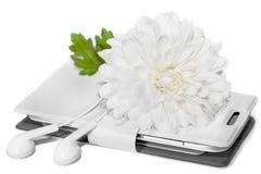 Flor blanca del crisantemo, del teléfono y de los auriculares aislados en el fondo blanco imagenes de archivo