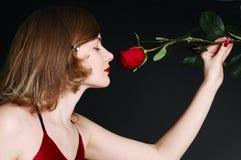 Flor color de rosa de la explotación agrícola hermosa de la muchacha en sus manos imagen de archivo libre de regalías