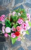 Flor colorida plástica en el fondo del piso de la roca Imagen de archivo libre de regalías