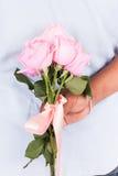 Flor cor-de-rosa da posse do homem atrás para a surpresa sua esposa Fotos de Stock