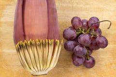 Flor da banana e uva roxa no fundo de madeira foto de stock royalty free