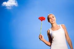 Flor da terra arrendada da mulher de encontro ao céu azul imagem de stock