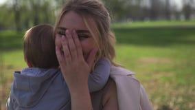 Flor de cerezo de Sakura - madre joven de la mam? que se sienta con su hijo del beb? del ni?o peque?o en un parque en Riga, Leton almacen de video