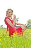 Flor de cheiro da jovem mulher em um prado Fotografia de Stock Royalty Free