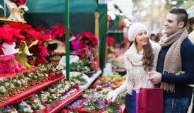 Flor de compra do Natal dos pares no mercado Fotografia de Stock Royalty Free