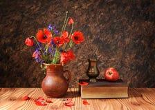 Flor de la amapola en un florero con una manzana Fotografía de archivo libre de regalías