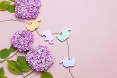 Flor de la hortensia del rosa de la lila y los juguetes de madera de los niños multicolores bajo la forma de elefantes en fondo r fotografía de archivo
