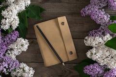 Flor de la lila en fondo de madera rústico con el cuaderno para el mensaje de saludo Visión superior Imágenes de archivo libres de regalías