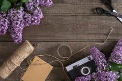 Flor de la lila en fondo de madera rústico con el espacio vacío para el mensaje de saludo Tijeras, carrete del hilo, pequeño sobr Imagenes de archivo