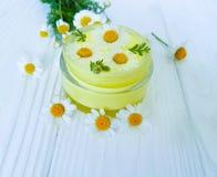 Flor de la manzanilla, crema cosmética de la crema hidratante del tratamiento en un fondo de madera imagenes de archivo