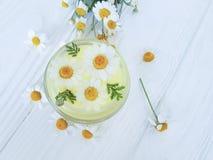 Flor de la manzanilla, crema cosmética de la crema hidratante en un fondo de madera imagen de archivo